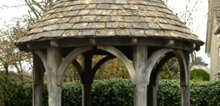 Cotswold stone tiles on a well house