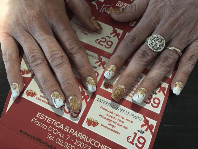 le unghie di una donna con smalto di color bianco e dorato