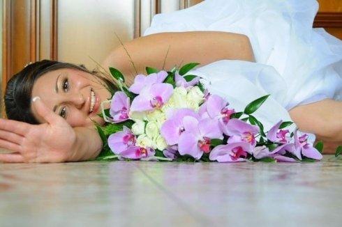 sposa sdraiata con bouquet