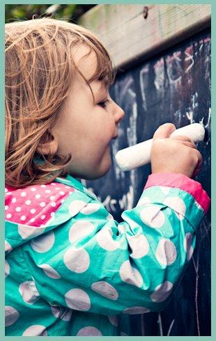 Girl writing something in chalk on a chalk board