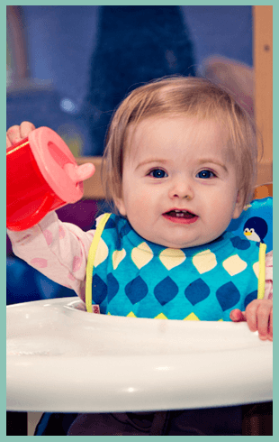 Girl in a high chair holding a plastic cup