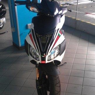 uno scooter bianco e nero con disegni della bandiera italiana sulla carena anteriore