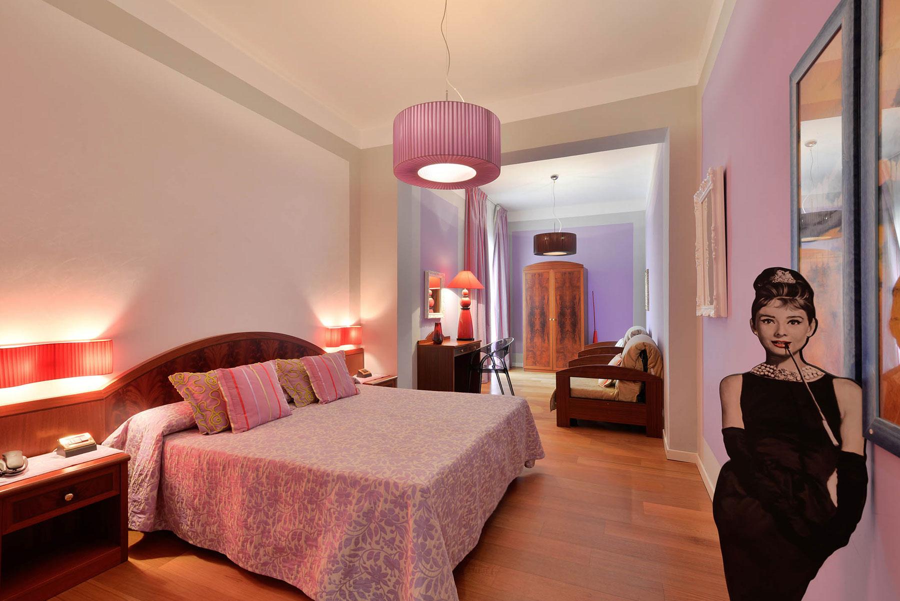Una camera con un letto matrimoniale,  un divano e una scrivania