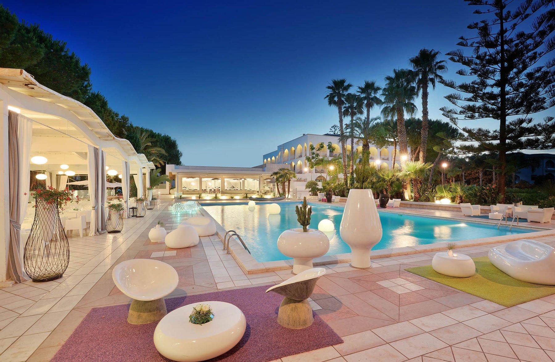 Una piscina di una villa con delle palme intorno