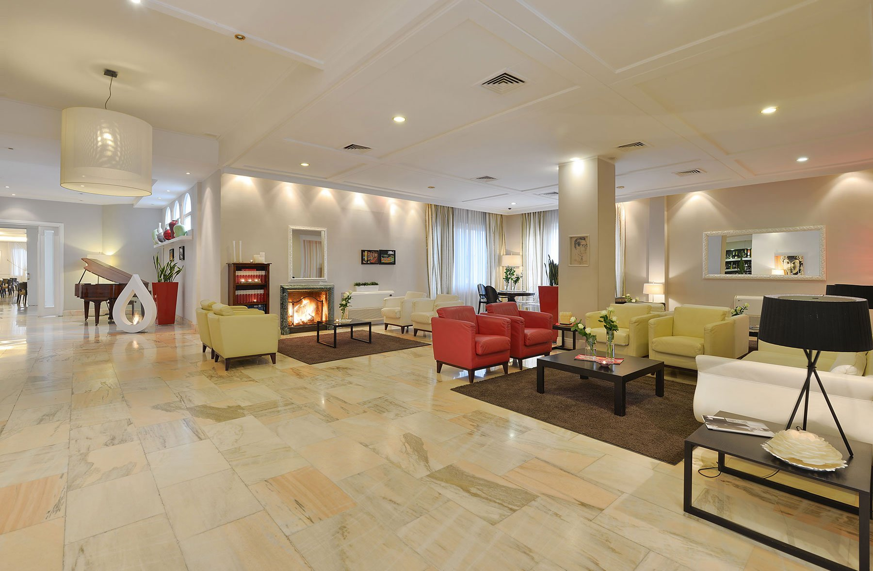 Una sala grande con poltrone,divani, un camino e un pianoforte