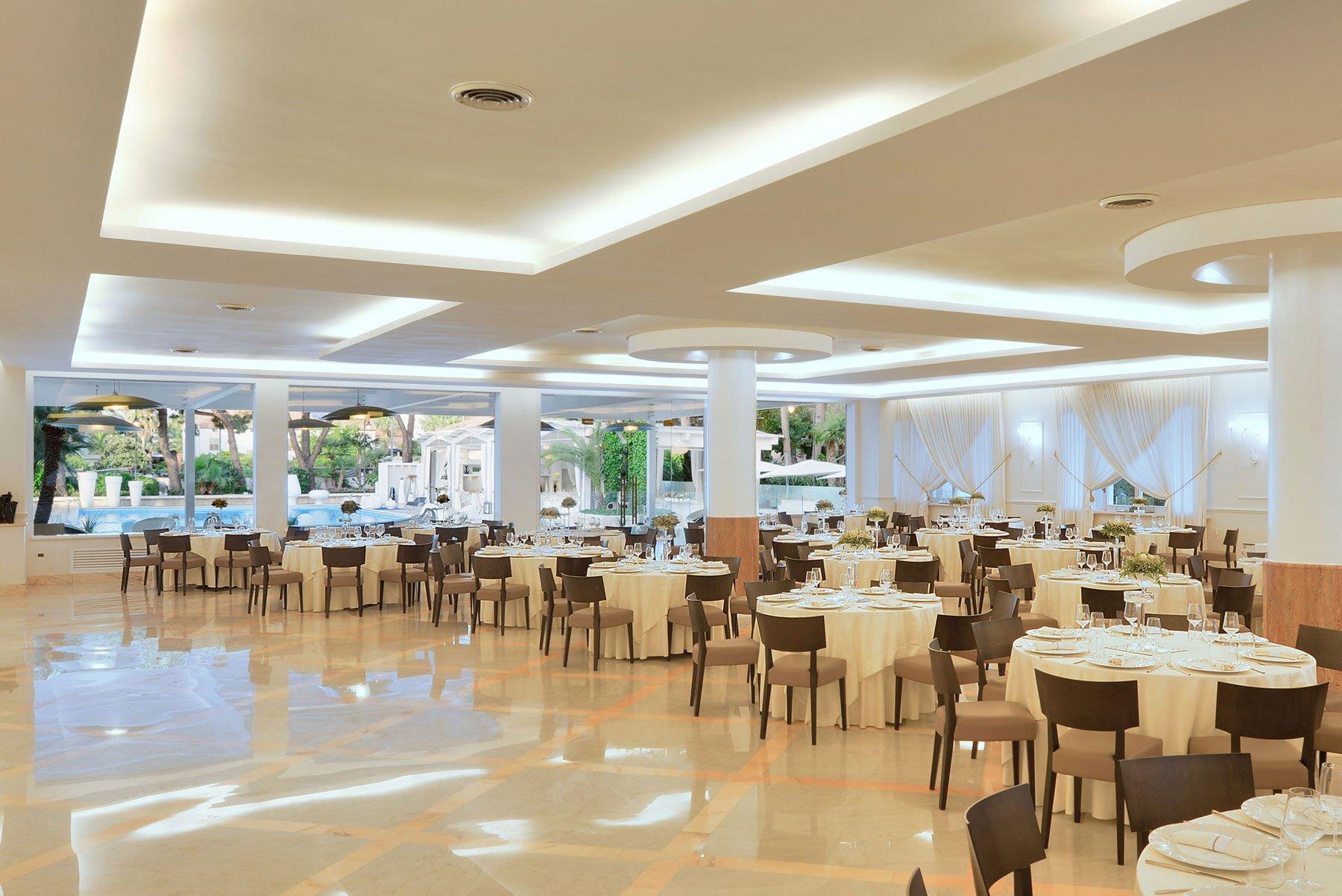 Dei tavoli con tovaglie bianche e delle sedie di color marrone