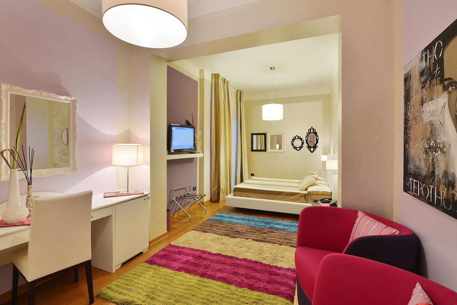 Una stanza con una scrivania e due poltrone di color fucsia