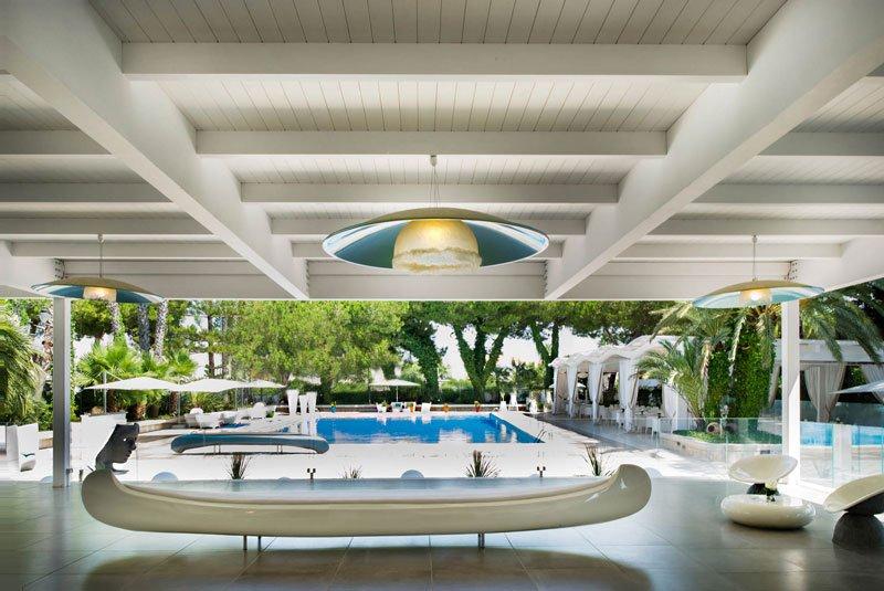 Una piscina e sulla sinistra dei tavoli sotto delle tende bianche