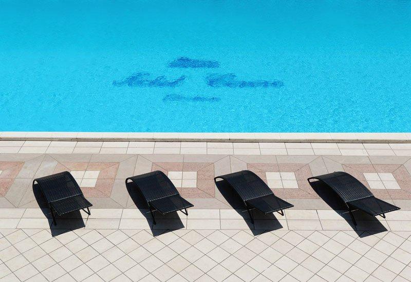 Una piscina e davanti quattro sdraio