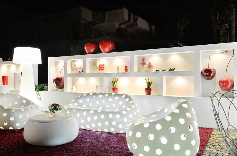 un divano e due poltrone all'esterno di color bianco e dietro delle decorazioni con delle ciliegie