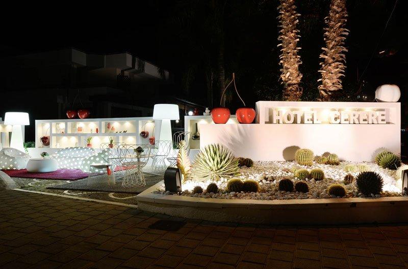 Un'aiuola con delle piante di cactus e dietro la scritta Hotel Cerere