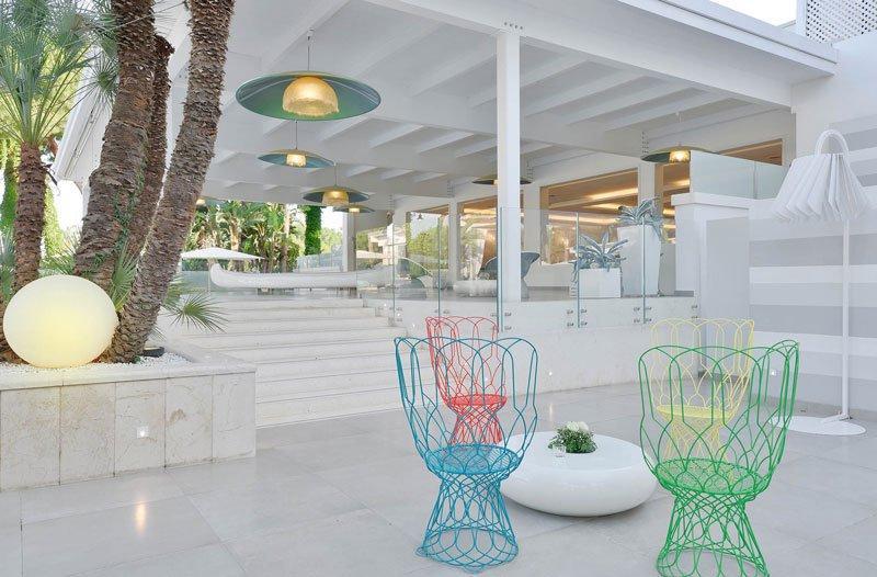 Quattro sedie di vari colori di metallo, sulla destra delle scale e vista dei lampadari a sospensione