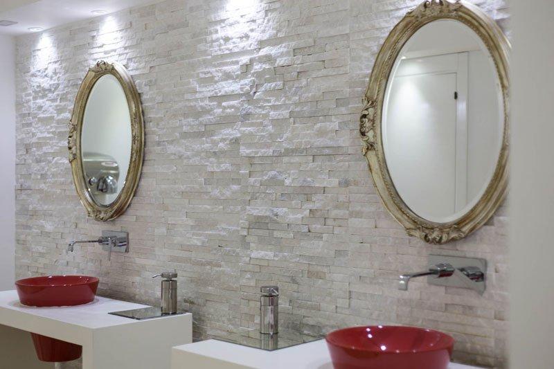 Un bagno con due lavabi di color rosso e due specchi