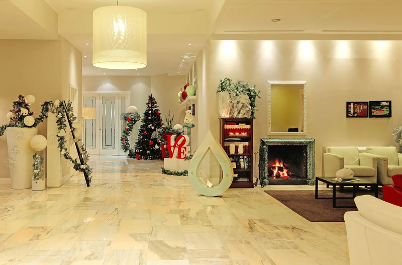 Una sala con dei divani di color bianco, un camino e un albero di natale in fondo