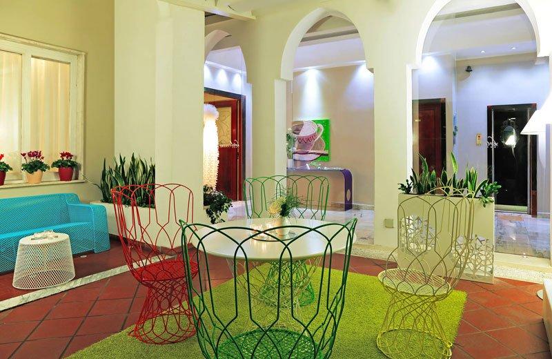 Una sala con un divano e delle sedie di metallo di varie colori