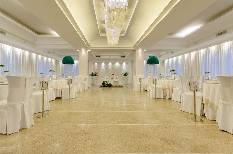 Una sala per ricevimenti con dei tavoli apparecchiati con delle tovaglie bianche