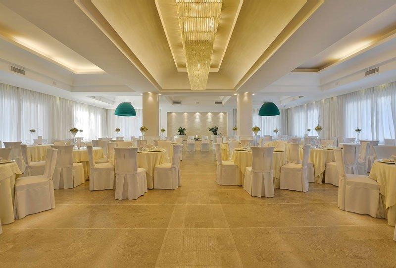 Una sala con dei lampadari, dei tavoli apparecchiati e delle sedie con coprisedie di color bianco