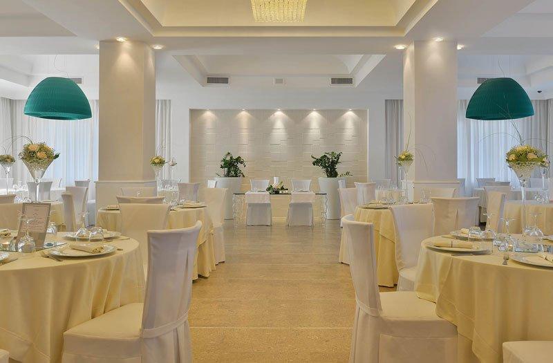 Una sala con dei lampadari a sospensione di color turchese e dei tavoli apparecchiati