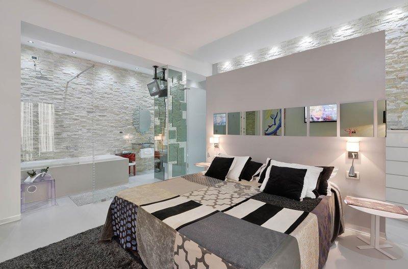 Una stanza con un letto matrimoniale e sulla sinistra un bagno con delle vetrate