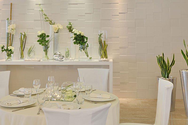 Un tavolo apparecchiato con dei piatti e dei bicchieri e dietro una mensola con dei vasi di fiori