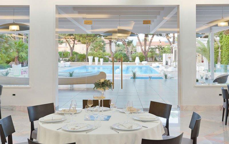 Un tavolo rotondo apparecchiato e attraverso le porte in vetro la vista di una piscina