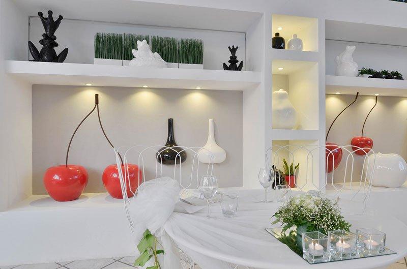 Un tavolo apparecchiato e decorato con dei fiori e dei lumini