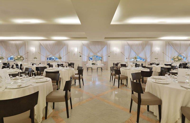 una sala con dei tavoli apparecchiati e in fondo delle finestre con delle tende bianche