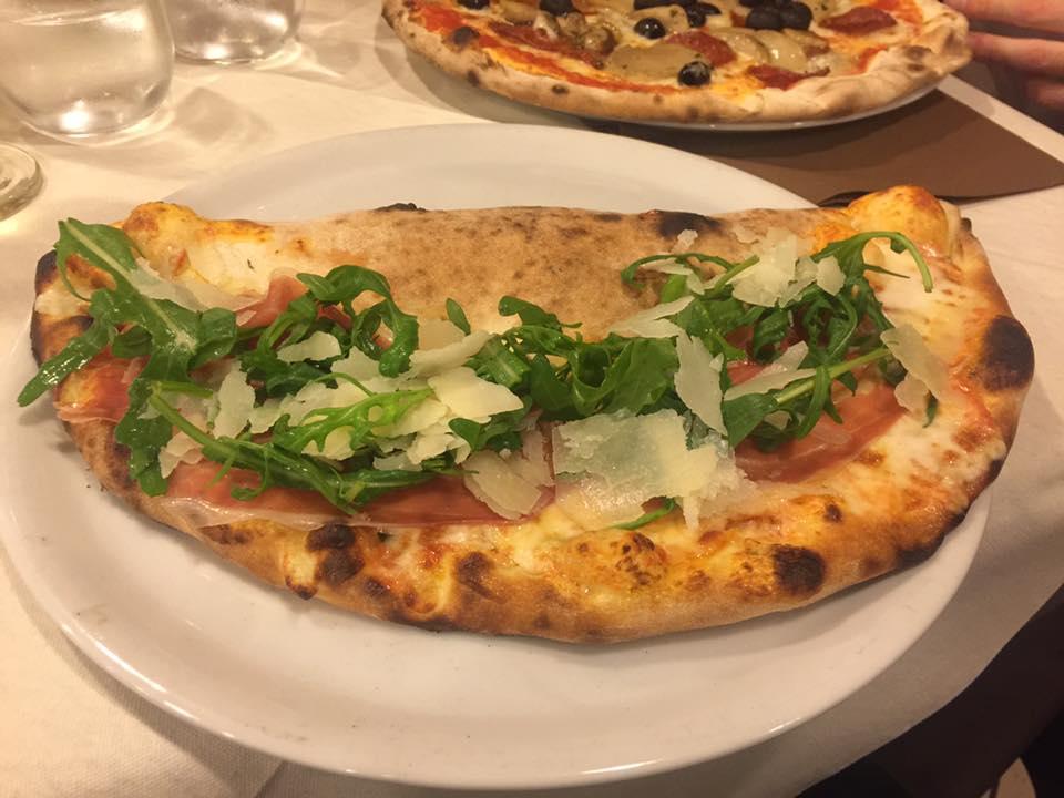 una pizza margherita con basilico su un tagliere