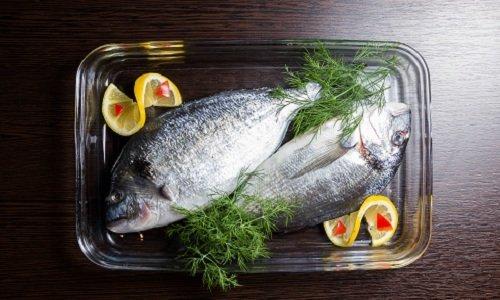 pesce fresco con aromi in un tegame di vetro