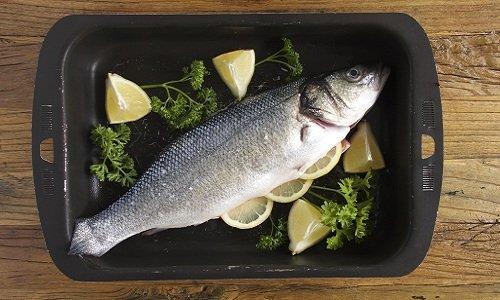 pesce fresco con limone in un tegame metallico