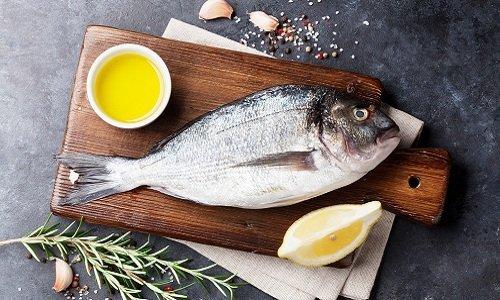 tagliere con pesce fresco, limone e un rametto di timo