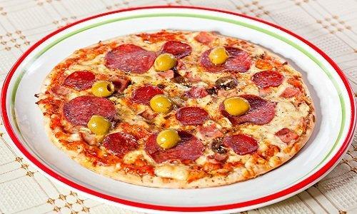 piatto con una pizza salame e olive verdi