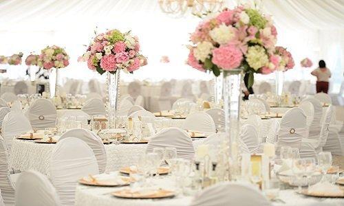 sala ricevimenti con tavoli e sedie bianchi decorati con fiori