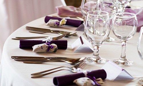tavolo bianco con set di bicchieri, posate e tovaglioli