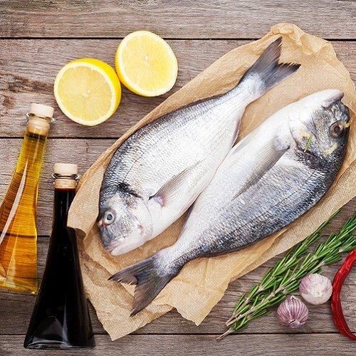 due pesci appena pescati con accanto spicchi di limone, aromi e condimenti