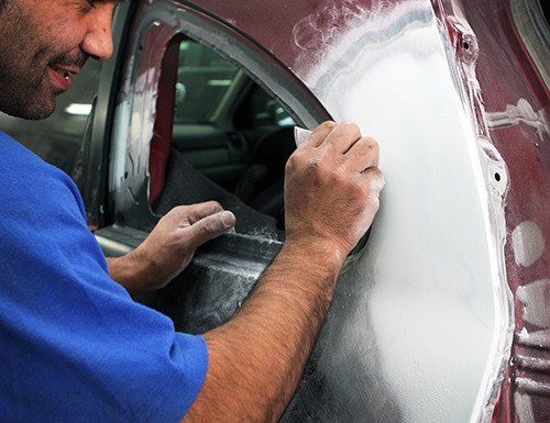 Worker Sanding a Vehicle