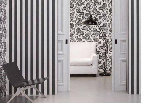 Combinazione in grigio e bianco sulle pareti a righe, fiori, sofà bianco, sedia grigia