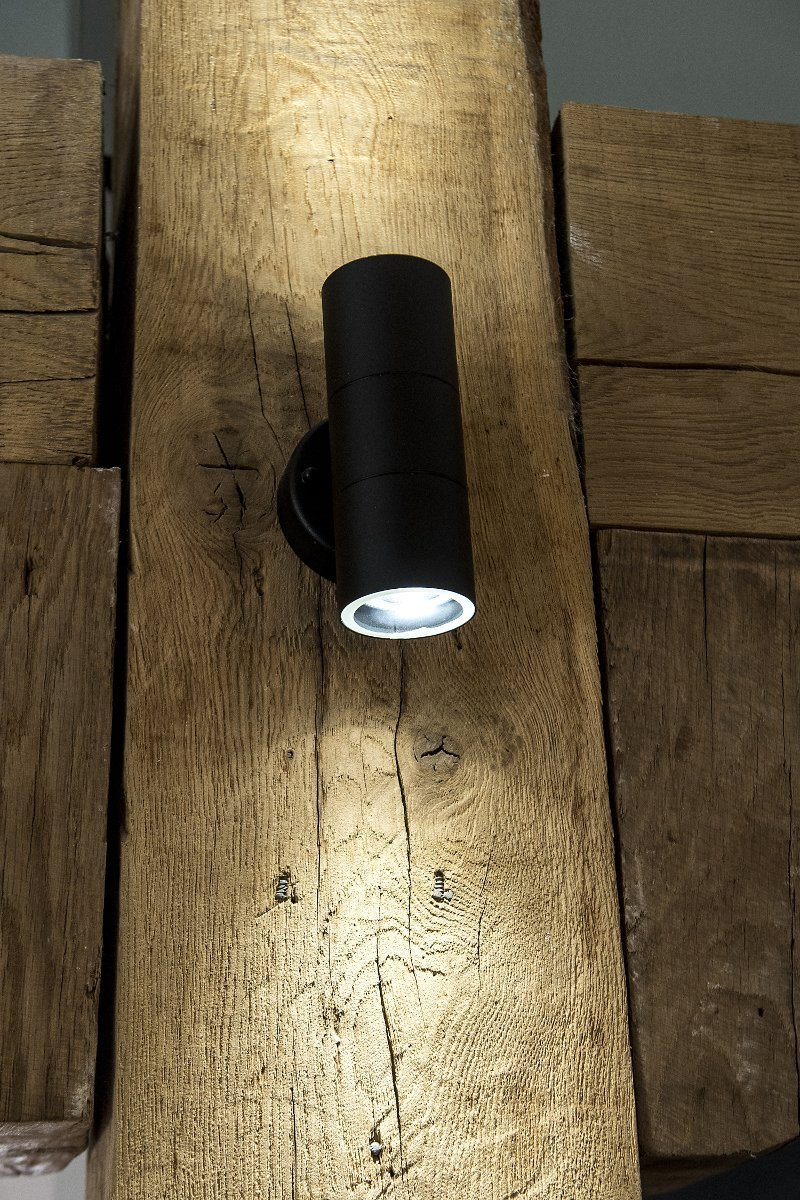 upwards and downwards pointing LED lamp shining onto a wooden beam