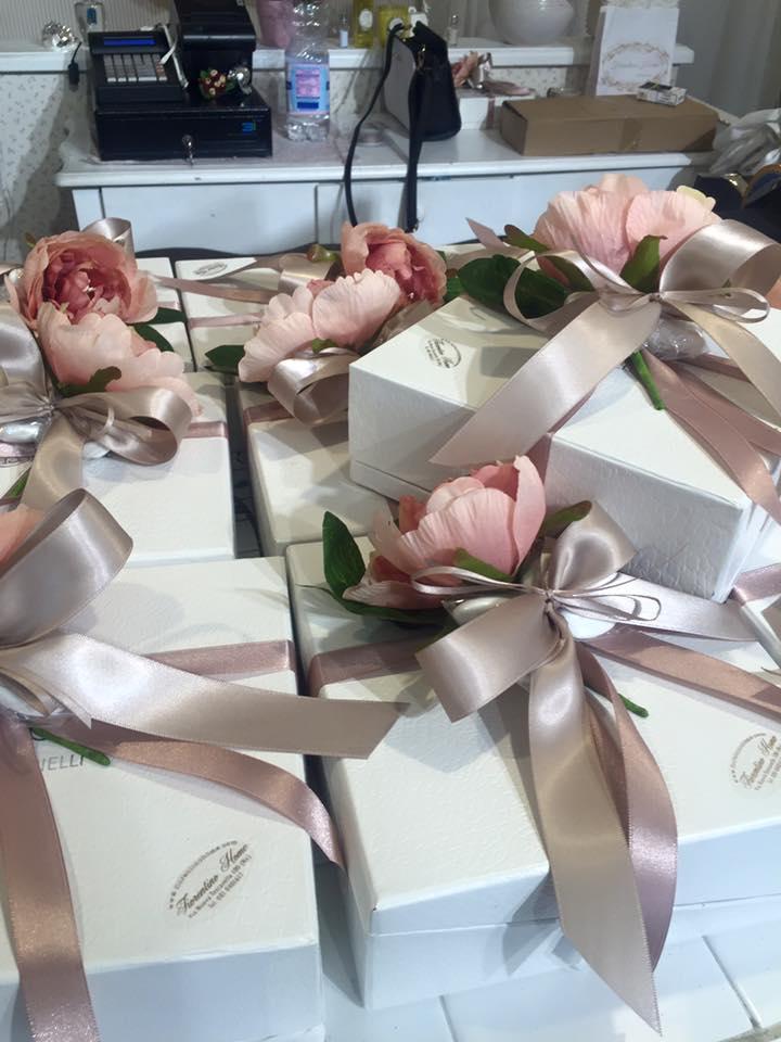 delle scatoline con dei nastri e fiori artificiali di color rosa