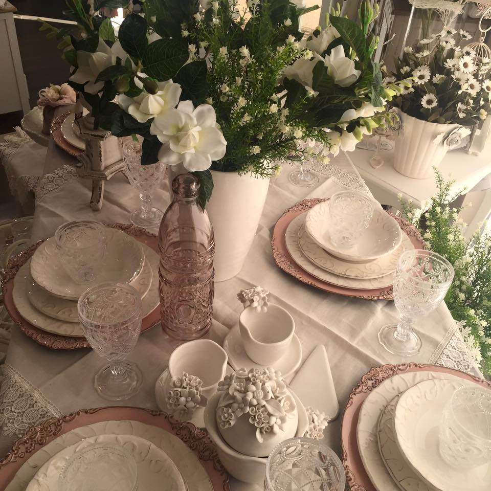 un tavolo con dei piatti di color bianco e rosa