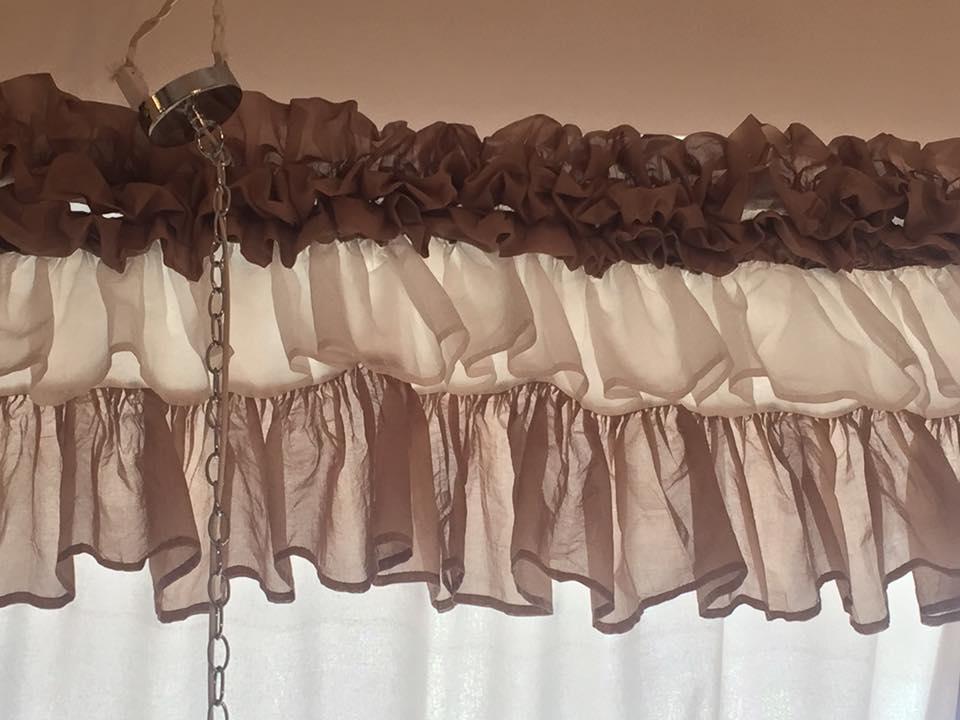 il bordo di una tenda con plissé di color marrone e bianco
