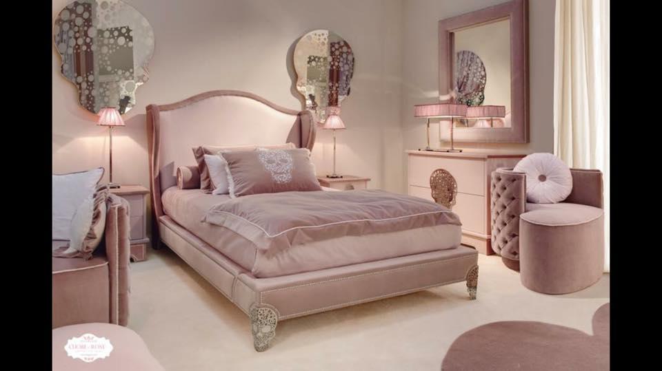 una stanza con letto,mobili e poltrone di color rosa