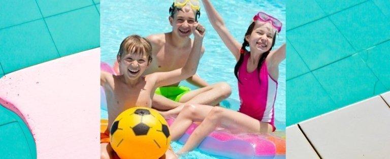 tre bambini che giocano in piscina con pallone e materassino