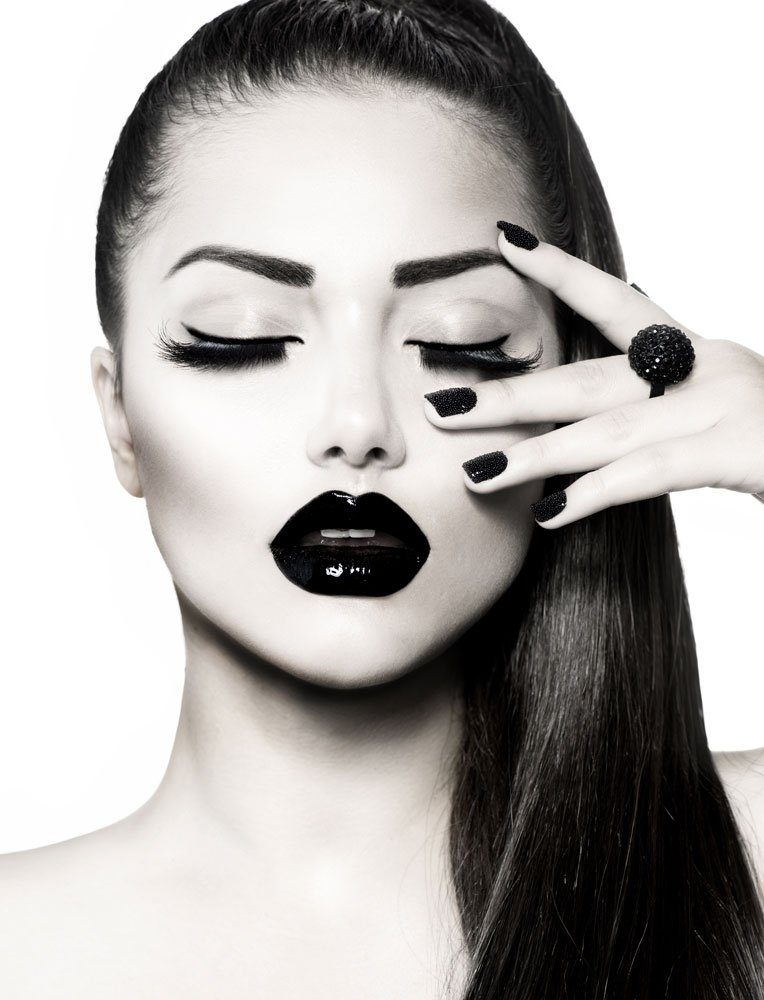 A black and white image of a woman with black nailpolish and lipstick