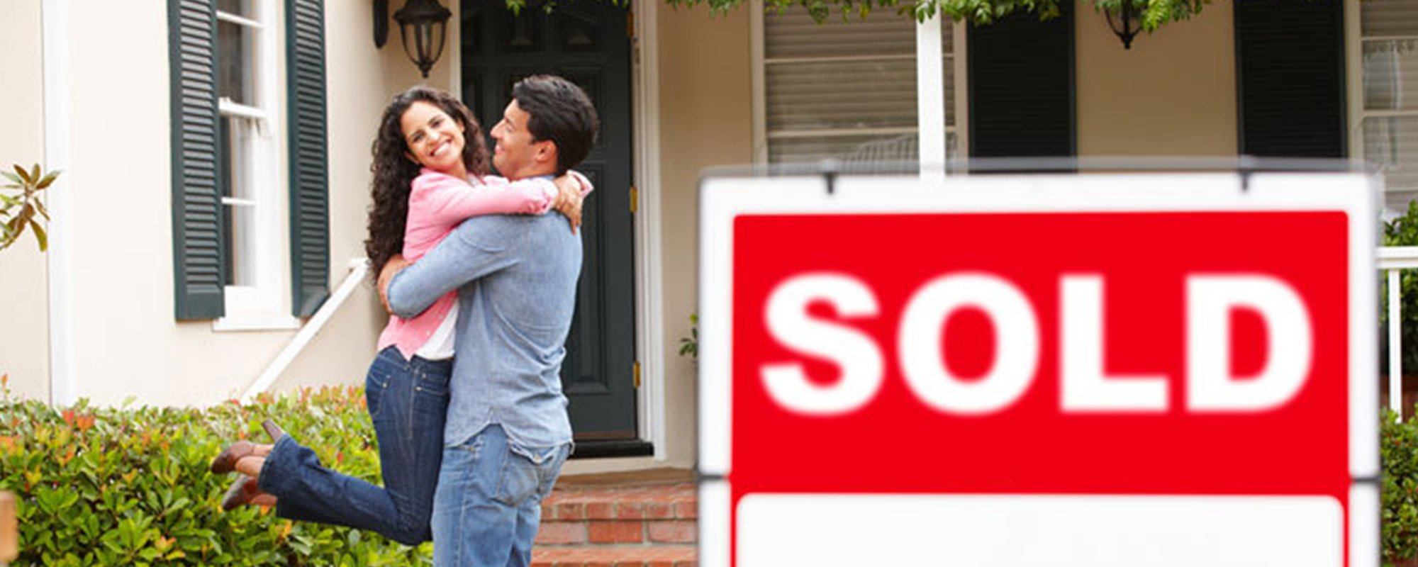 Happy couple standing at the property with sold signage