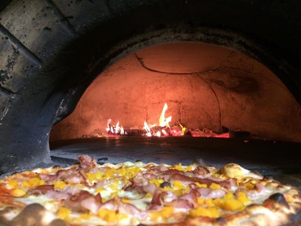 Pizza con base pomodoro e mozzarella, con aggiunta di zucca a dadini e pancetta