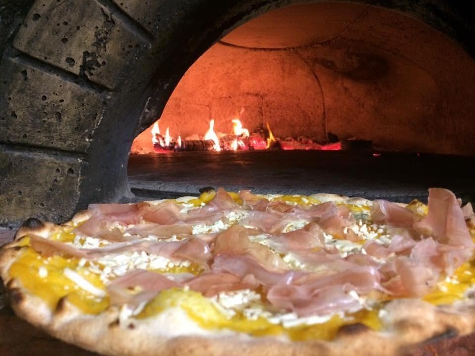 Pizza con base crema di zucca, tocchetti di gorgonzola e a fine cottura scaglie di ricotta affumicata e speck