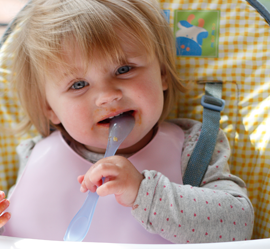 a small girl biting spoon