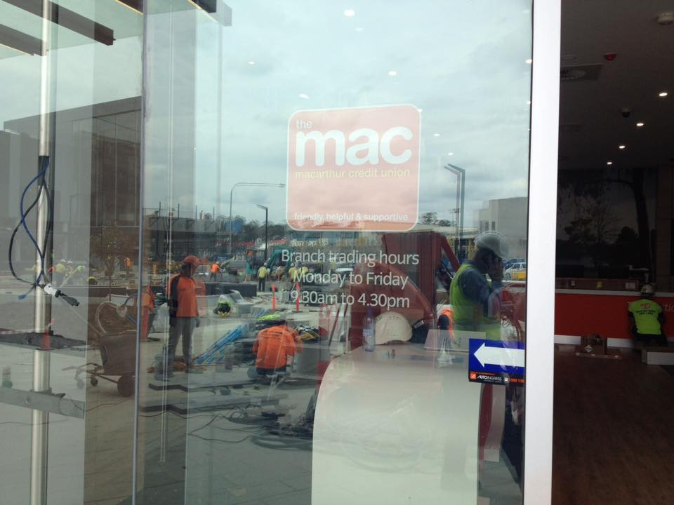 mac sign on window relfecting workers outside