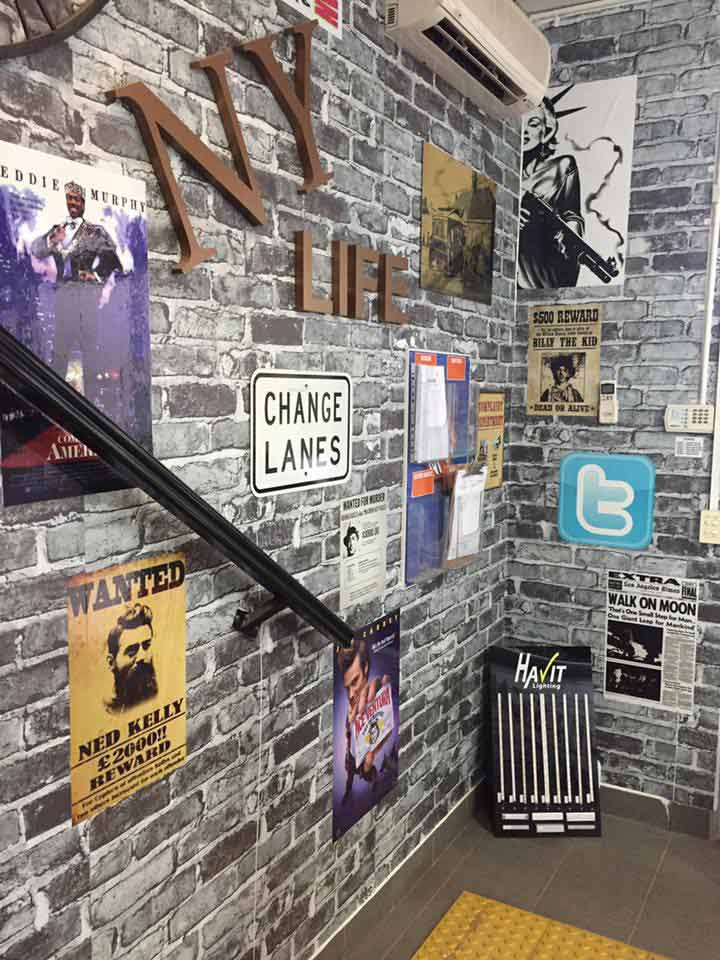 gray brick wall with signs and the stairway handrail
